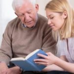 Photograph of an elderly gentleman looking at a book with a young woman